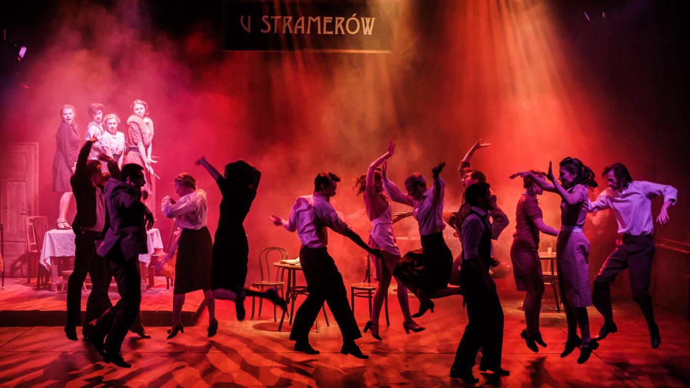 Scena zbiorowa. Grupa energicznie tańczących ludzi na tle czerwonych świateł. Dużo teatralnego dymu. Nad nimi szyld U STRAMERÓW.